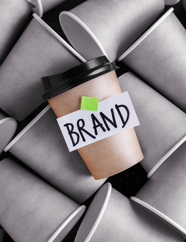 "Stylized image of a coffee cup labeled ""brand"" standing out from gray coffee cups, representing branding"