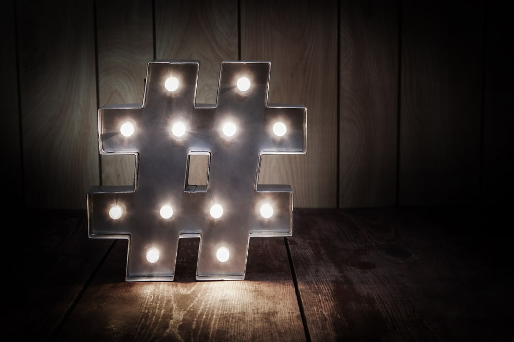 A lit-up hashtag symbol against a wood background